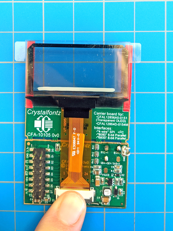 Display inserted into ZIF connector on breakout board with finger to close ZIF connector