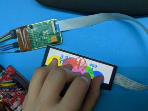 """Display connected to a PCB. A hand is touching the display with five fingers. At each touch point, the display is showing a different colored circle. The display also says """"3.9"""""""" and shows the Crystalfontz logo"""