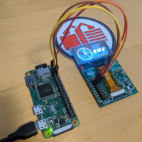 a transparent OLED with blue pixels displaying a clock. Under the display is a sticker with the crystalfontz logo that is partially visible through the display. The display is on a breakout board connected to a raspberry pi zero