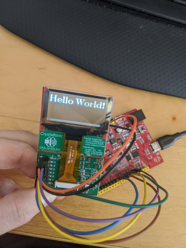 """The transparent OLED on the CFA10105 oled breakout board connected to a seeeduino. The OLED is displaying the words """"Hello World!"""""""