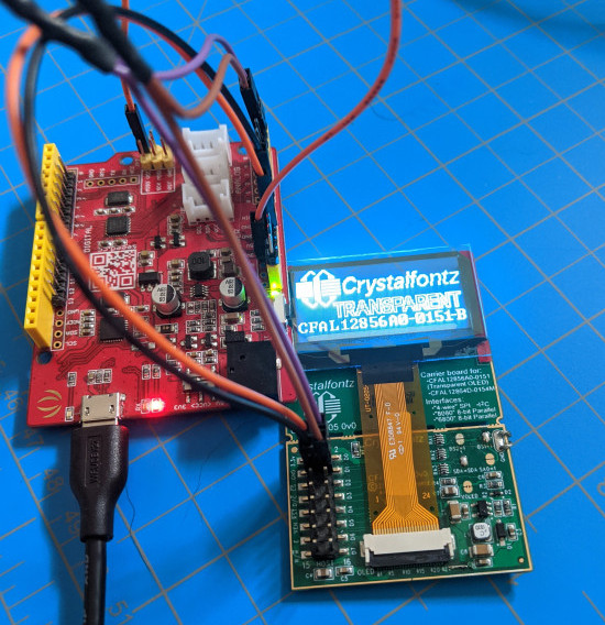 """A transparent OLED on a CFA10105 breakout board connected to a Seeedunio using four wires. The OLED is displaying the Crystalfontz logo and the words """"Crystalfontz Transparent CFAL12856A0-0151-B"""""""