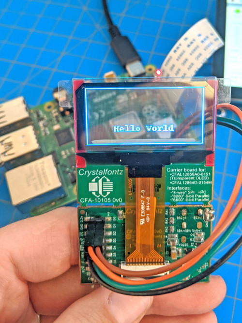 """transparent oled displaying """"hello world"""" with raspberry pi visible through the display"""
