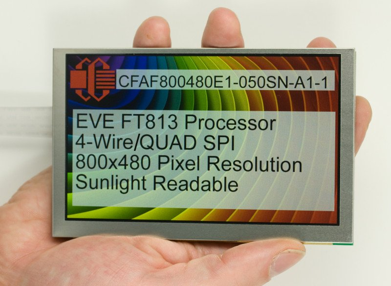 A 5 inch LCD TFT held in a hand for scale. Display shows a rainbow screen, the Crystalfontz logo, and text: CFAF800480E1-050SN-A1-1 EVE FT813 Processor 4-Wire/QUAD SPI 800x480 pixel resolution Sunlight Readable